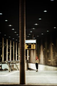 girl standing next to concrete pillar at night